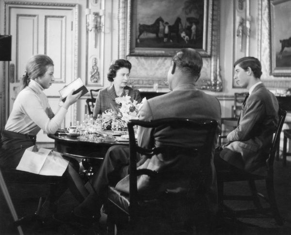 Queen Elizabeth II and her husband Prince Philip, Duke of Edinburgh pictured sitting around the dinner table with their two eldest children, Prince Charles and Princess Anne. Date: 1969