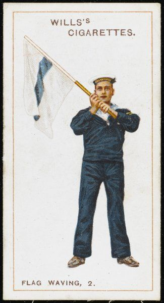 A signalman of Britain's Royal Navy signals with a flag