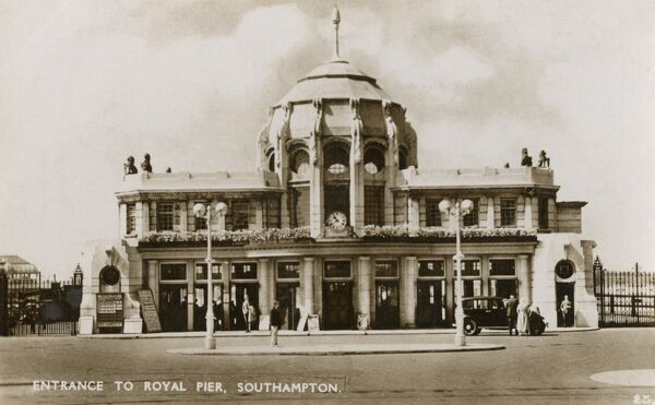 "Entrance to the Royal Pier, Southampton. The pier pavilion was extended in 1922 and the present gatehouse, described at the time as ""wedding cake architecture"", was opened in 1930 (designed by Edward Cooper Poole)"