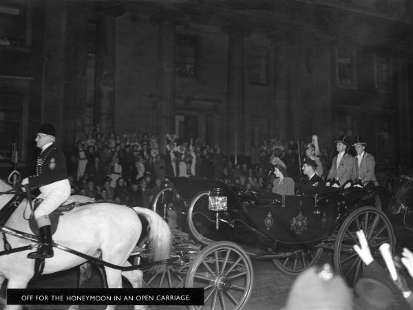Princess Elizabeth (Queen Elizabeth II) and her new husband, Prince Philip, Duke of Edinburgh leave Buckingham Palace in an open carriage to embark on their honeymoon which would be spent at Broadlands in Hampshire
