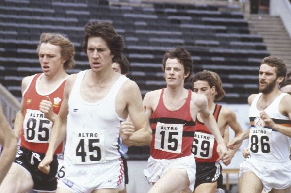 Runners jostling for position on the race track. Date: 1980