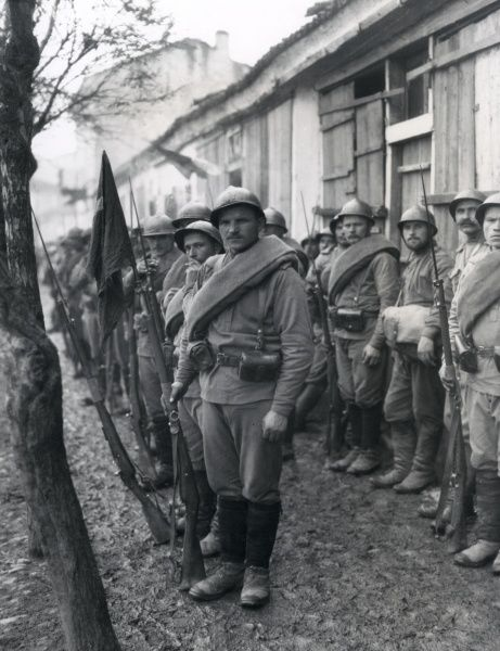 Russian troops with fixed bayonets awaiting word to enter Monastir on the Salonika Front in Macedonia during the First World War. They are screened against the walls to protect them from shell fire and enemy planes. Date: circa 1916