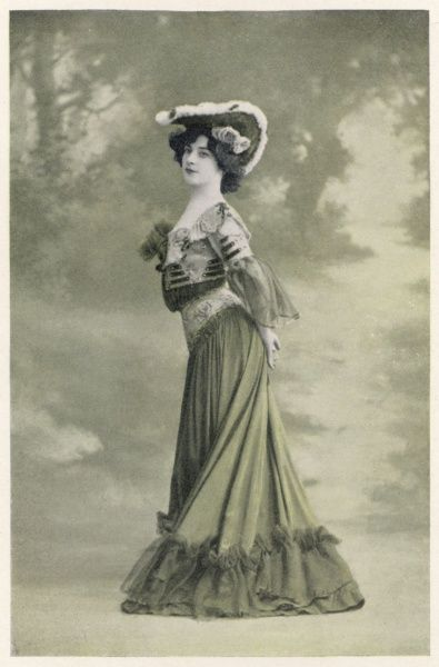 An example of the S-Bend silhouette. The heavily ornamented bodice is pouched over the waist giving a disjointed effect. The yoke on the skirt emphasizes the hips