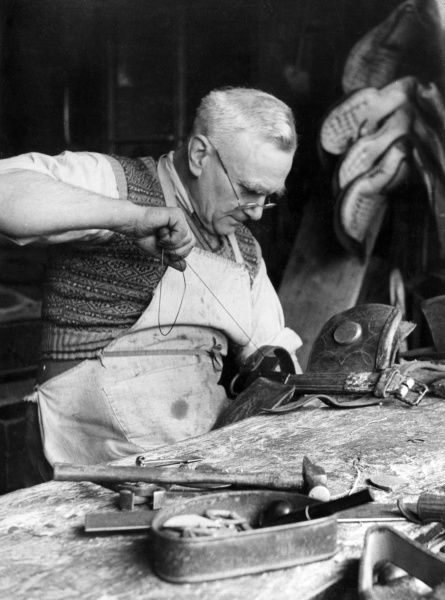 An old saddler repairs a horse saddle. Date: 1960s