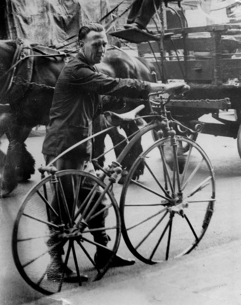 A man wheels a Safety Bicycle, an early form of bicycle from the 1890s which replaced the Penny Farthing. However, he obviously does not think it safe enough to ride through Holborn, London!