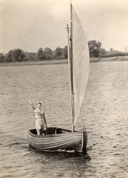 View of Hickling Broad in Norfolk with a lady, wearing shorts and beret waving from a sailing or wherry boat