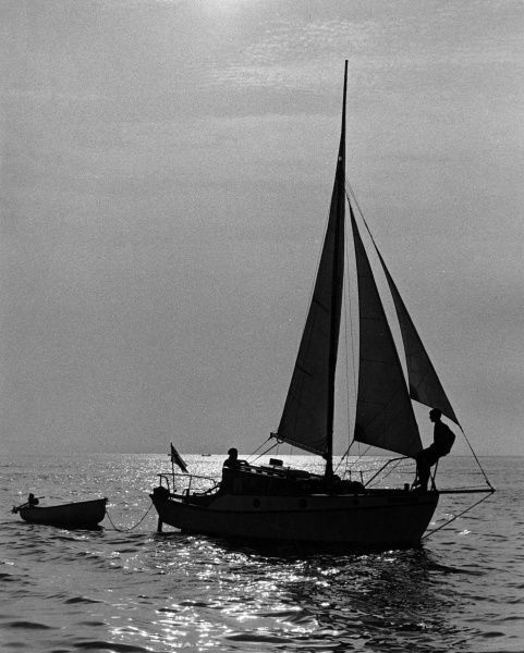 The sun glistens on the water as a boy and his father enjoy a leisurely evening sail off Shoreham, Sussex, England. Date: 1960s