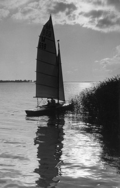 A leisurely sunset sail. Date: 1930s