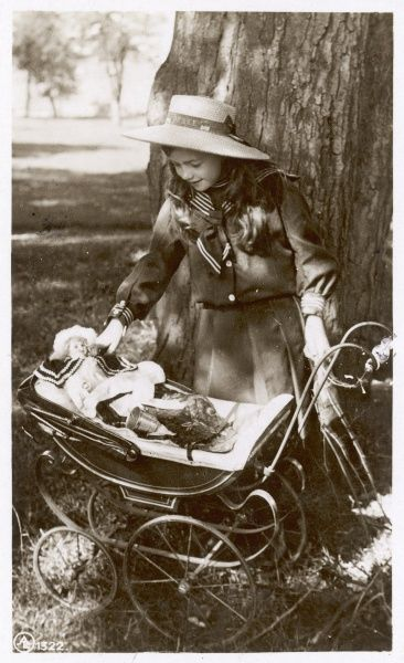 A girl dressed in a sailor inspired outfit prepares to take her dolly for a ride in a pram