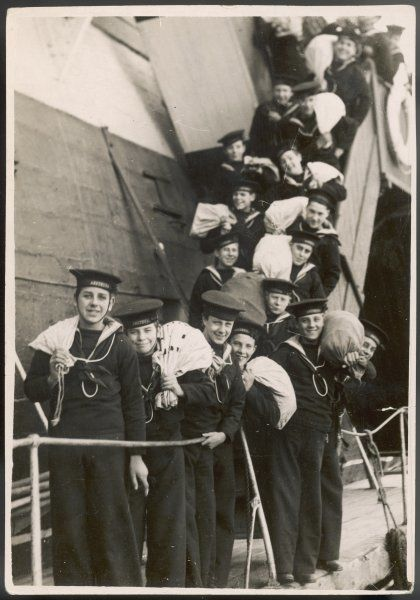 The smiling boys of the H.M. Training ship 'Arethusa' off on leave for their Christmas holidays with their kit-bags slung over their shoulders