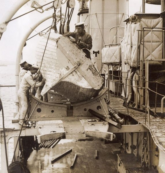 Men of the British Royal Navy undertaking repairs on a boat on board a ship during the First World War. Date: 1914-1918
