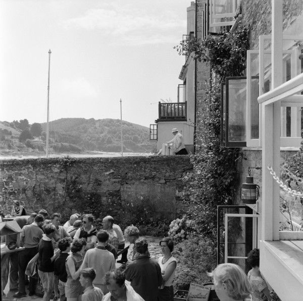 Drinking in a pub garden, or the exterior seating area for a Hotel Bar at Salcombe, Devon. Photograph by Norman Synge Waller Budd