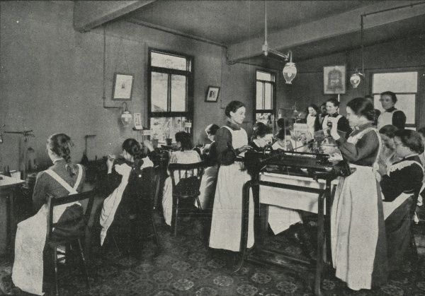 Girls at work in a Salvation Army knitting factory. They are all wearing regulation long white aprons