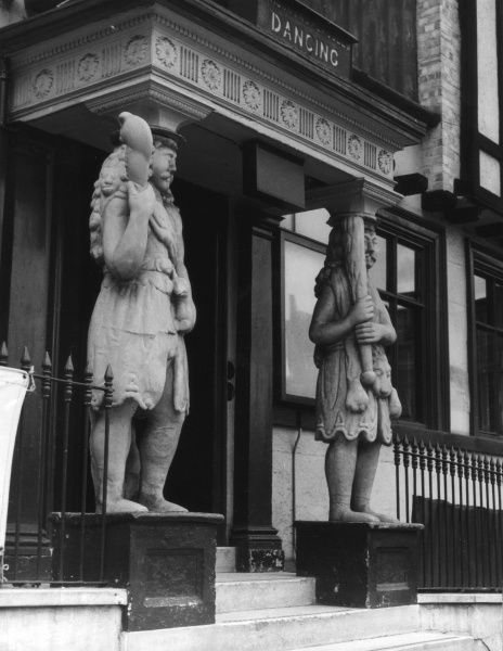 'Samson' and 'Hercules', two great wooden figures, supporting the porch of the Samson and Hercules Mansion, built by Christopher Jay in 1657, Tombland, Norwich. Date: 17th century