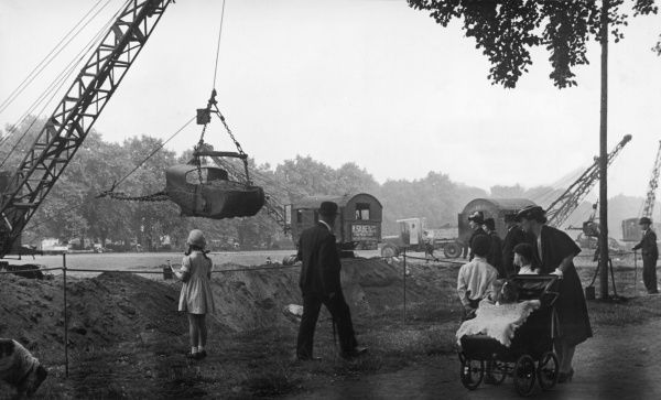 Mrs. Storer and family stop to watch excavators at work in Hyde Park, London, digging earth for sand bags during World War II