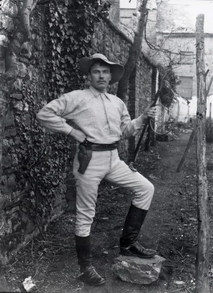 A lion tamer with Sanger's Circus poses in costume by a wall, with his foot on a large stone, during a visit to Haverfordwest, Pembrokeshire, Dyfed, South Wales