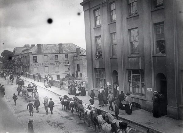 View of Salutation Square during Sanger's circus procession, in Haverfordwest, Pembrokeshire, Dyfed, South Wales, with boys following in the roadway, and people watching from the pavements and from windows