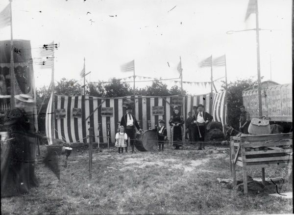 Scene at Sanger's Circus during its visit to Haverfordwest, Pembrokeshire, Dyfed, South Wales, showing a USA-themed stall in a field. There is a striped windbreaker which, as the notices say, has been kindly lent by Mr John North