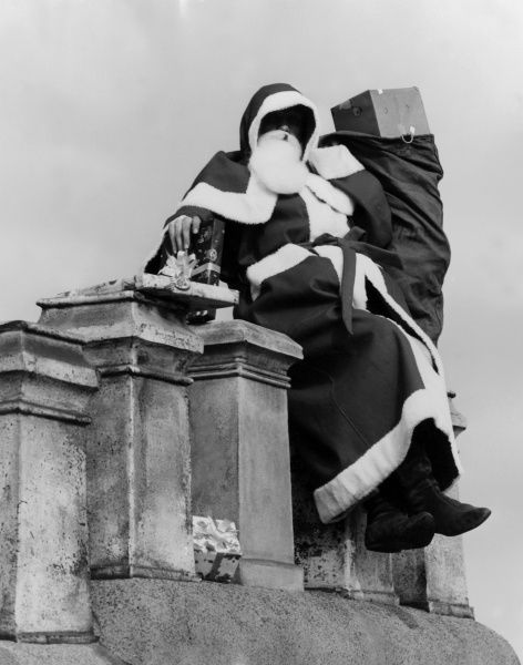 Father Christmas dropping presents down a chimney. Date: 1960s