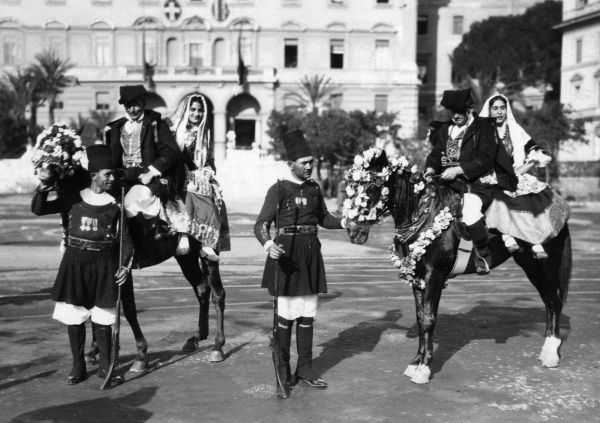 Sardinian men and women in traditional costume, their caparisoned horses decorated with flowers for a festival or wedding. Date: 1930s