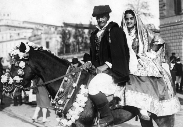 A man and woman in traditional Sardinian costume, with their gaily caparisoned steed. Date: 1930s