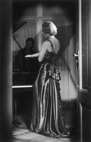A blonde woman wearing a long satin evening dress with a bow at the back and a slight train poses thoughtfully by a piano