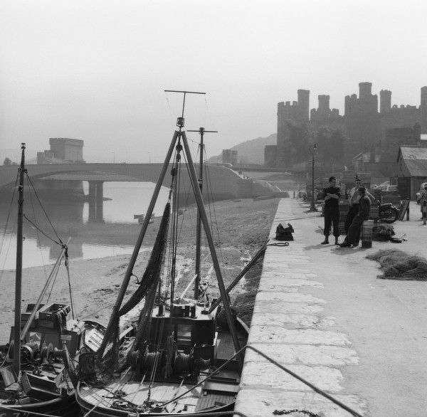 A wonderful, atmospheric view of Conwy Harbour, North Wales, with the silhouette of the Castle in the background. Photograph by Norman Synge Waller Budd