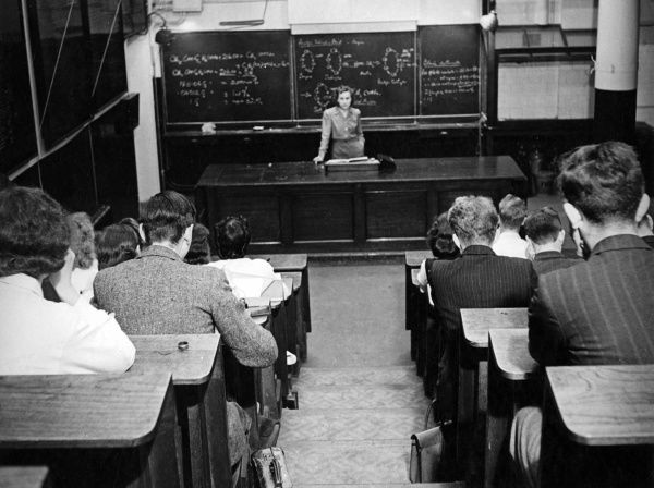 Scene in a lecture theatre, with chemical equations written on the blackboard, a woman giving a lecture, and students taking notes