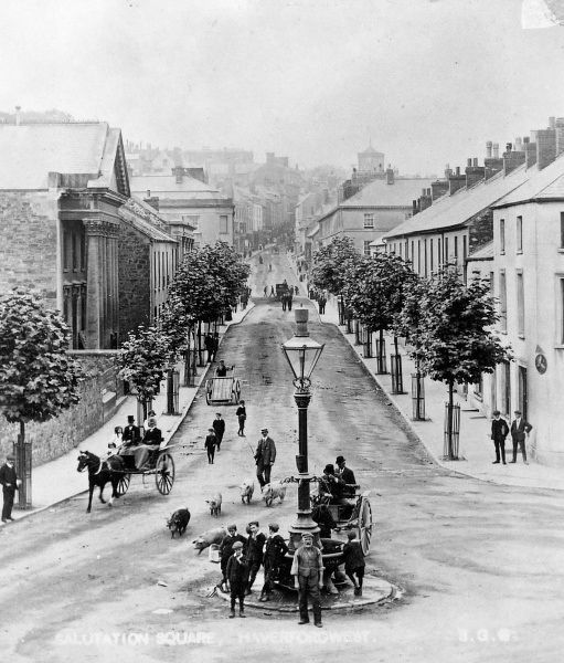 A street scene in Salutation Square, Haverfordwest, Pembrokeshire, Dyfed, South Wales, with traffic and pedestrians. The lamppost at the centre doubles as a water trough for horses