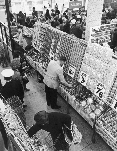 A scene in a Tesco supermarket. Many of the items are on special offer and there is quite a long queue at the checkout. There are several promotional signs for Green Shield Stamps