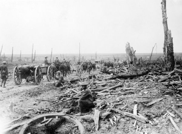 A scene on the Western Front during the First World War, with soldiers travelling along a country road by horse and cart, and debris at the roadside. Date: 1914-1918