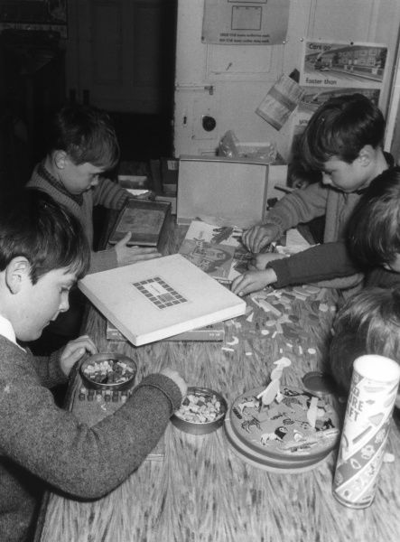 Children playing board games in a classroom. Date: 1960s