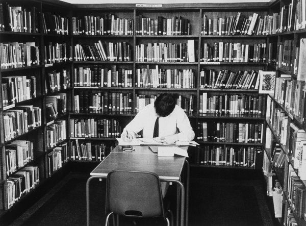 Studying in a quiet part of the school library. Date: 1950s