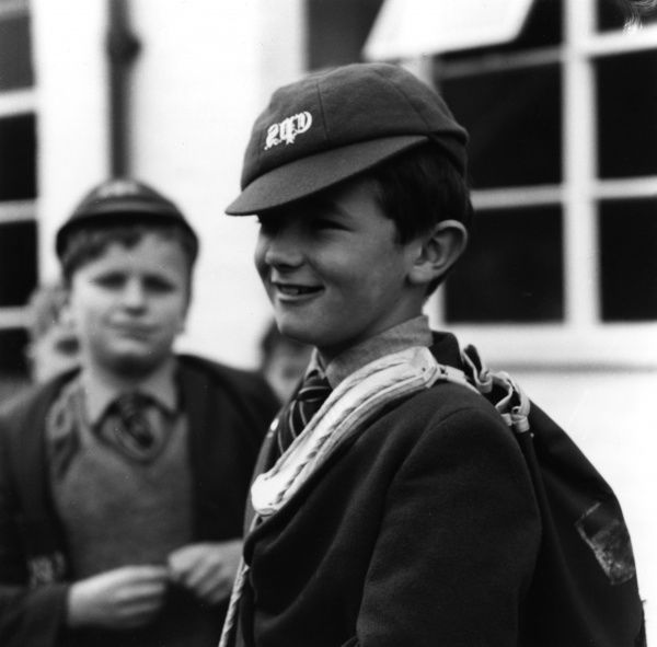 A schoolboy in uniform; he wears his cap slightly crooked. Date: 1965