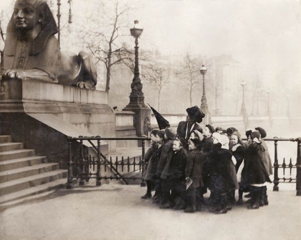 A class of London County Council schoolchildren on a trip to Cleopatra's Needle on the Thames Embankment, Central London. Their teacher points with her umbrella and tells them all about it
