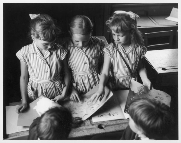Three schoolgirls in summer dresses look intently at drawings on the desk in front of them
