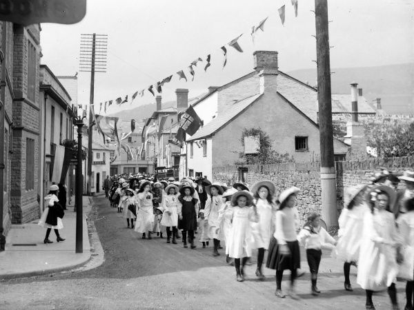 A long line of local schoolgirls parade along Beaufort Street in Crickhowell, Powys, Mid Wales. The street is decorated with flags and bunting, perhaps to celebrate Empire Day (24 May)