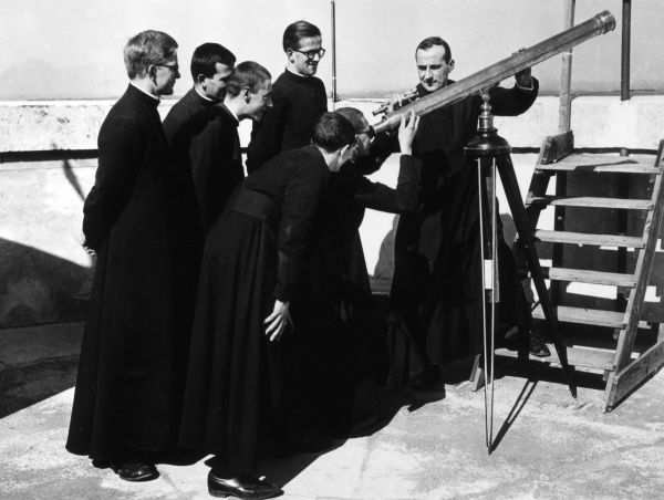 A group of Italian priests making astronomical observations through a telescope at the Torre Metrologica, Rome, Italy. Date: 1930s