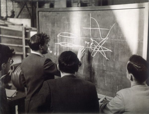 A group of scientists study a problem by using diagrams on a blackboard