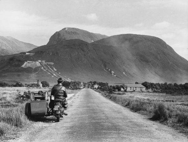 Tourists in a motorcycle and sidecar take in this fine view of the distant peak of Ben Nevis, Britain's highest mountain, from the 'Road to the Isles', Inverness-shire
