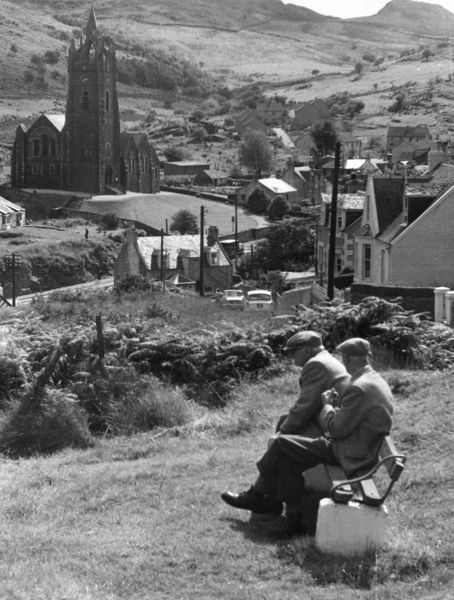 Old men sitting on a bench overlooking the town of Tarbert, with its fine church, on Loch Fyne, Argyllshire, Scotland. Date: 1960s