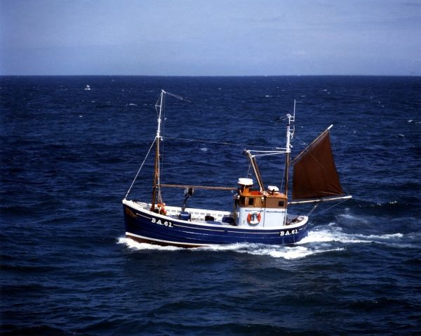 A 45 foot Scottish-built inshore wooden fishing boat, out at sea on a relatively calm day