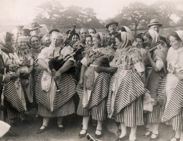A jolly group of Scottish fishwives and some of their menfolk. One of the women plays the bagpipes