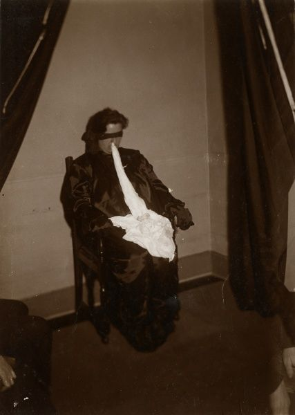 "Photograph of the Scottish medium Helen Duncan blindfolded during a sance with ""ectoplasm""' from her nose gathering on her lap, May 1931. HPG/1/4/2 (xx)&quot"