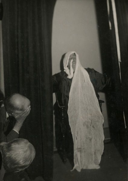 "Photograph of the Scottish medium Helen Duncan during sance with ""ectoplasm"" wrapped around her head and the end tucked into her nostrils, May 1931. HPG/1/4/2 (x)&quot"