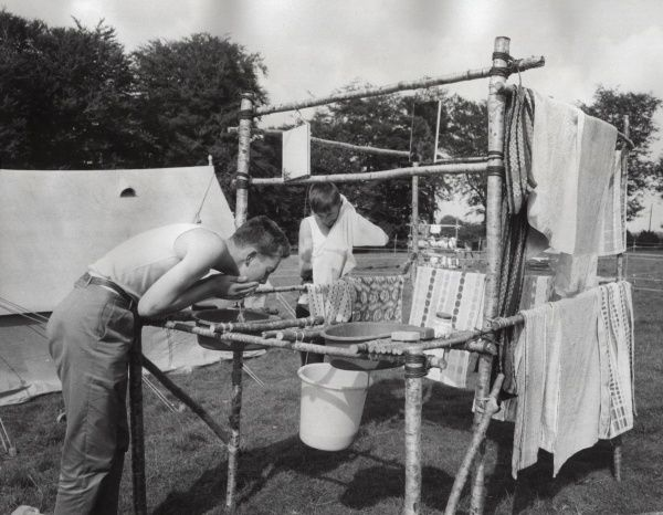 A Scout in camp washing himself before morning inspection. The boys themselves have built the washstand cum clothes dryer for the material available on the campsite. They brought the buckets and basins themselves!