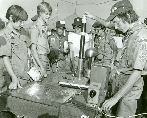 One American Boy Scouts demonstrates some equipment in a Scout-built project to show another group of Scouts the principles of static electricity. The Arts and Sciences Expo was a new feature at Jamboree East & West 1973
