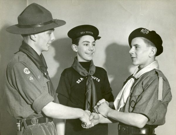An Air Scout shakes hands with both a Sea Scout and a Scout to celebrate the formation of the Air Scouts