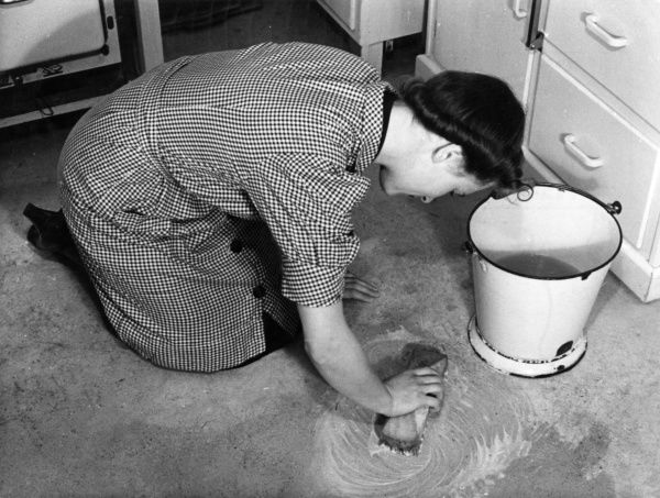 A housewife kneels down as she scrubs the kitchen floor with a scrubbing brush and an enamel bucket of water. Date: 1940s