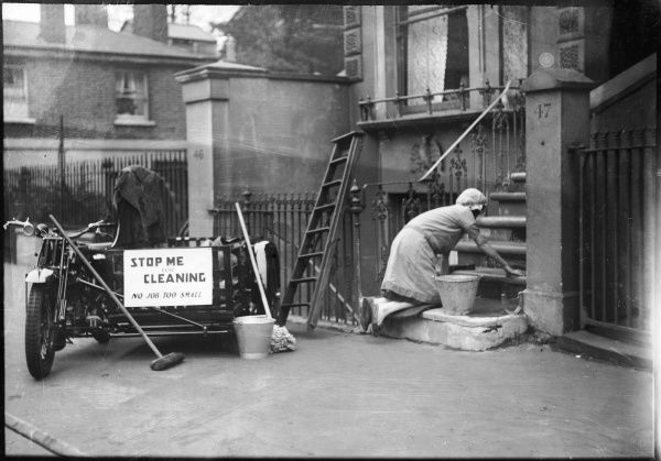 A Charwoman, who goes to work in her motorcycle and side car, kneels whilst scrubbing the steps of no. 47